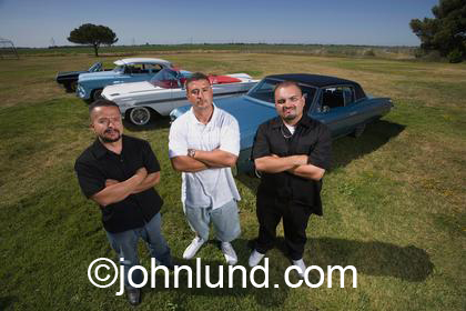 Portrait of three Hispanic men who are classic car owners.  The Latino men are standing in a green grassy field near Tracy Northern California.